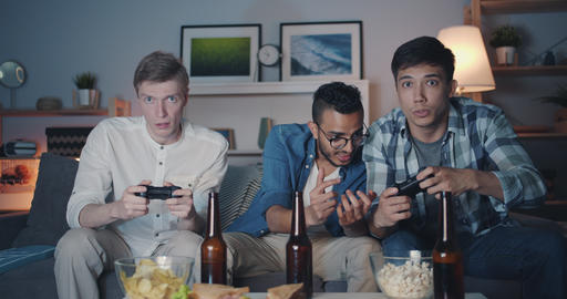 Portrait of happy men playing video game at home at night looking at camera Filmmaterial