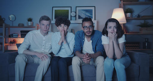 Frightened students watching thriller on TV with scared faces at night at home Filmmaterial