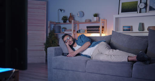 Arabian man sleeping on couch in front of TV relaxing at night in dark flat Filmmaterial
