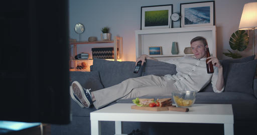 Happy young man watching TV drinking beer relaxing on couch at night Filmmaterial