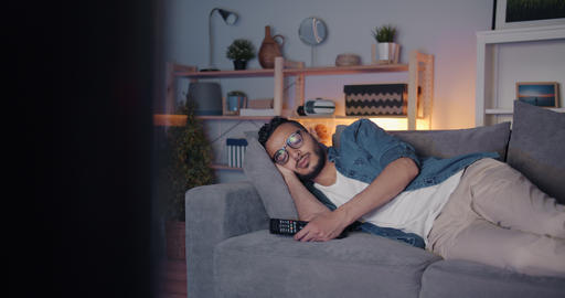 Tired Middle Eastern man sleeping on couch in front of TV lying alone Footage