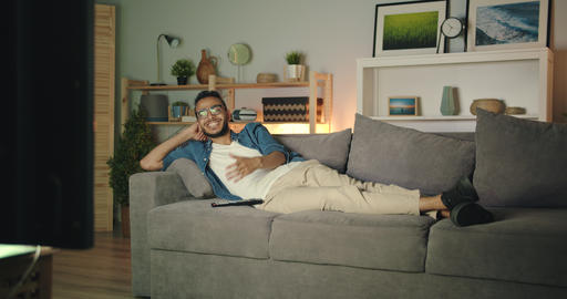 Carefree Middle Eastern guy watching TV laughing lying on couch in dark house Filmmaterial