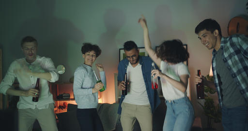 Excited girls and guys dancing at home party holding bottles with drinks Filmmaterial