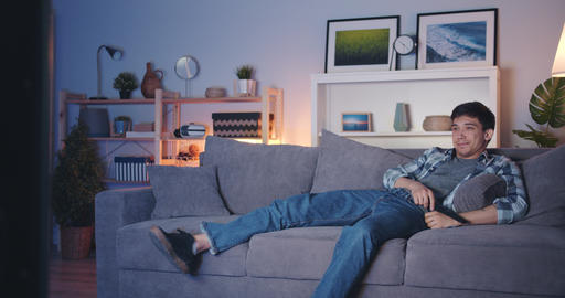 Cheerful person laughing watching TV chilling on couch in dark apartment Footage