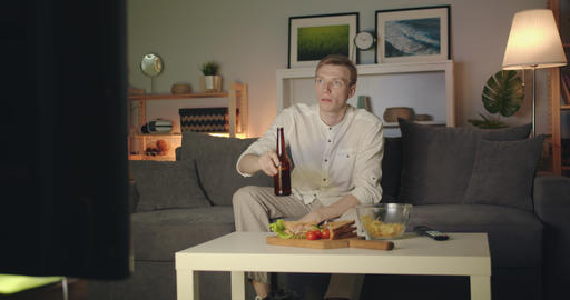 Shocked man watching TV drinking beer spilling drink at night at home Filmmaterial