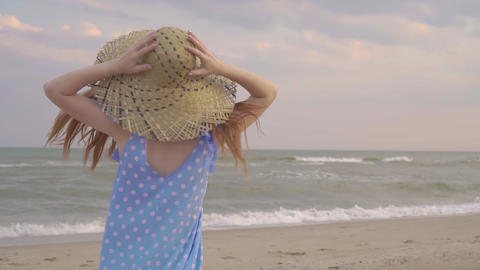 Carefree woman dancing on the sunset on the sea beach. Girl rotate in the straw Footage