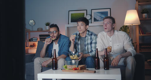 Friends watching TV with attention eating snacks holding bottles at night Filmmaterial
