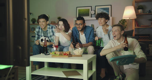 Group of friends watching football on TV at night clinking bottles having fun Filmmaterial