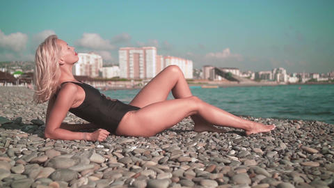 Young sexy girl in a swimsuit lying on a rocky seashore. Blonde in a one-piece Live Action