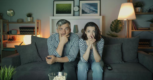 Shocked girl and guy watching TV with serious faces touching face at night Footage