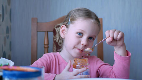 Beautiful Little Girl Kid Eats by Spoon Fruit Puree or Sauce Footage