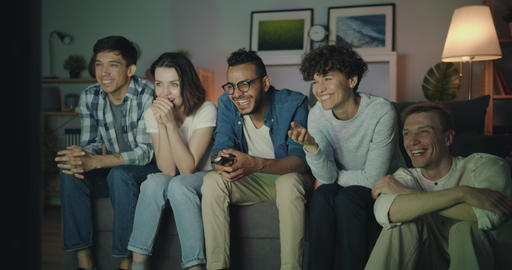 Joyful students watching funny comedy on TV at night laughing having fun Filmmaterial