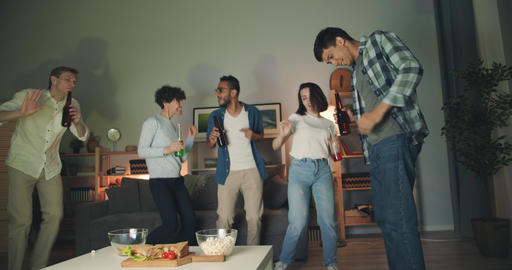Multiracial group of young people dancing clanging bottles at home party Filmmaterial