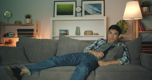 Mixed race man student watching TV clicking remote control at night alone Filmmaterial