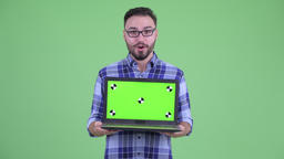 Happy young bearded hipster man showing laptop and looking surprised Filmmaterial