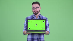 Stressed young bearded hipster man showing laptop Filmmaterial