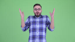 Happy young bearded hipster man looking surprised Footage