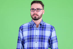 Face of young handsome bearded hipster man thinking Photo
