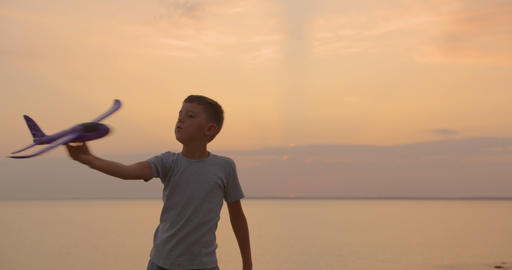 Happy kid playing with toy airplane against orange sun summer. Best childhood Live Action