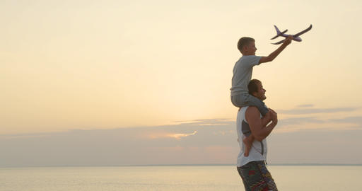 Happy father and son playing with airplane toy together at sunset happy family Live Action