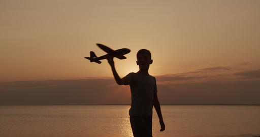 Happy child runs with a toy airplane on a sunset background. Childhood dreams Live Action