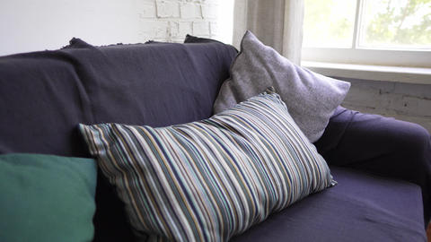Close-up of a sofa by the window, a cozy interior in natural materials in design Live Action