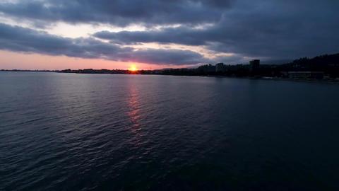 Sun at sunset Reflected on the sea seashore cityscape sunset on the horizon Footage