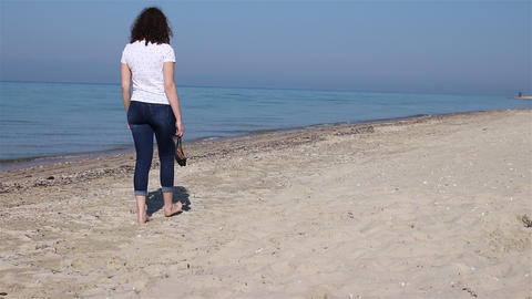 Young woman walking slowly on the beach taking shoes in hands and walk barefoot Footage