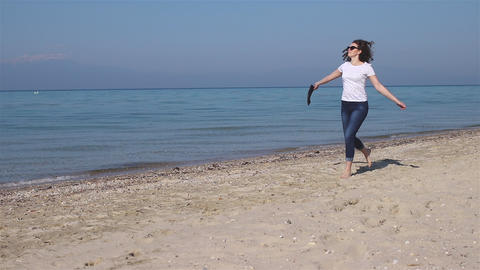 Happy young woman running on the beach barefoot and take shoes in hands. Feel free and happy Live Action