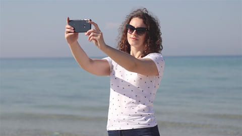Young and beautiful woman take selfies on the beach on the sunlight Footage
