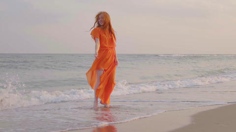 Carefree woman dancing on the sunset on the sea beach. Girl spinning. Femininity Footage