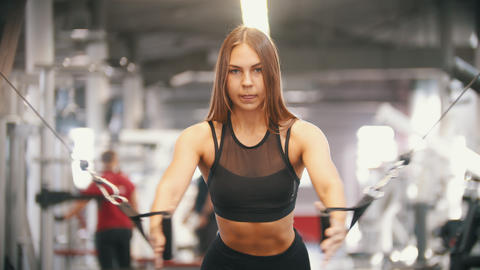 An athlete woman training in the gym - pulling the handles - pumping chest Footage