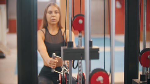 An athlete woman in sports clothes training in the gym - pulling the handles Footage