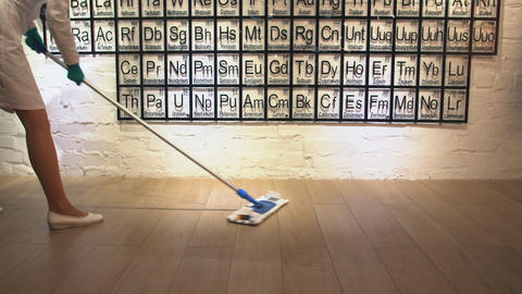 Woman cleaning parquet floors in chemical laboratory with the periodic table on Live Action
