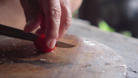 Old lady cutting tomato above wooden board. Traditional way Footage