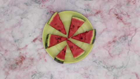 looping footage of slices of fresh and organic watermelon moving on green plate. Stop motion Animation