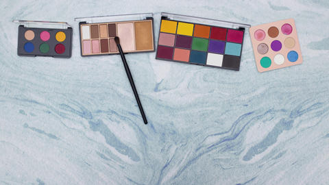 Eye shadow palettes appear and make up brush smear on the colors. Stop motion animation Animation