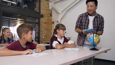 Young teacher of elementary school walking among between desks puts textbooks Live Action