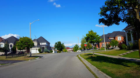 Viewpoint of Suburban City Street With Vehicle Traffic. Urban Road Along Residential Suburb Houses Footage