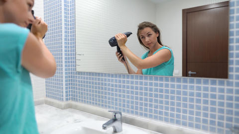 Pretty woman blows her hair in front of bathroom mirror Live Action