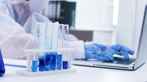 Close up of scientist typing on her laptop and smoking blue fluid in test tubes Live Action