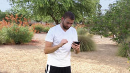 Young Male Millennial Plays Pokemon Go-Style Game in Public Park Footage