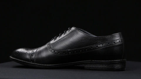 Rotation of a stylish classic black shoe with laces on a black background Live Action