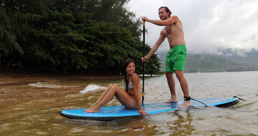 Stand up paddleboard - couple on paddle board in ocean watersport activity Footage