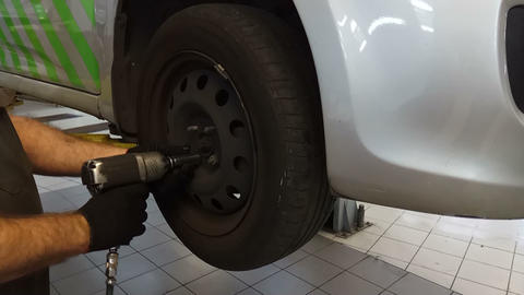 master car mechanic unscrews a car wheel in a car dealership Live Action