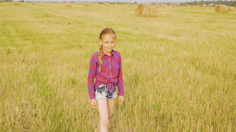 Cheerful girl running to haystack at yellow meadow. Playful girl teenager Live Action