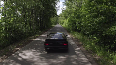 Aerial view black jdm car driving on countryside road among green woodland. Back view from flying Footage