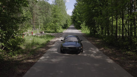 Black car moving on countryside highway on green forest background drone view. Aerial view old Footage