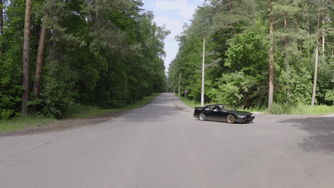 Japanese car moving on countryside road and turns. Drone view japanese low car driving on country Live Action