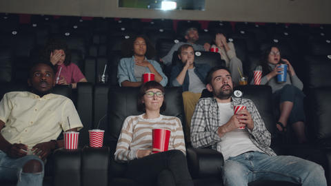 Group of people girls guys watching horror film in cinema expressing emotions Live Action